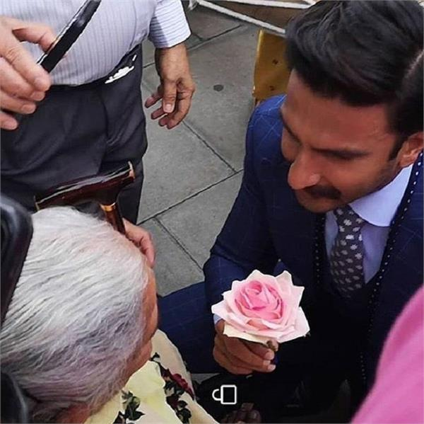 bollywood actor gives rose to lady in wheelchair